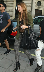 Miley packed all her daily essentials in an over-sized leather bag while traveling in London.