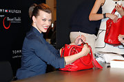 Milla matched her red lips to her bold red tassled tote bag. Cute!
