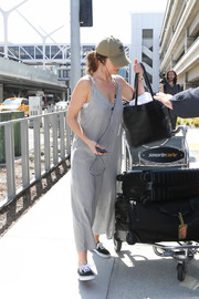 Minka Kelly arrived on a flight at LAX looking casual and youthful in loose gray jumpsuit.