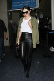 Miranda Kerr looked tough-chic in a Saint Laurent military jacket teamed with high-waisted leather leggings while catching a flight.