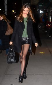Miranda kept warm (despite those tiny shorts!) in her classic black coat while out in NYC.