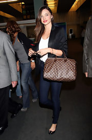 Miranda Kerr accented her classic street attire with a brown canvas checkerboard bag.