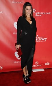 Gina Gershon added a pop of color to her black outfit with a red frame clutch when she attended the 2013 MusiCares Person of the Year Tribute.