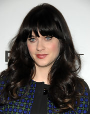 Zooey Deschanel wore her hair in her signature style with long curls and lash-length bangs at PaleyFest 2012.