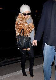 Nicole bundled up in a fur jacket and black knee-high boots.