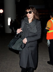 Noomi Rapace bundled up in a black embossed scarf for her travels at LAX.