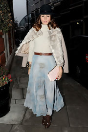 Olivia dons a bowler hat with her eclectic ensemble at London Fashion Week.