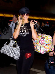 Paris Hilton channeled her inner Barbie as she made her way through LAX carrying a Barbie Generations of Dreams duffle.