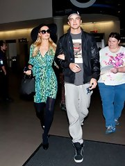 Paris Hilton chose a leopard-print green and blue dress for her travel look.