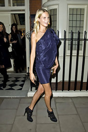 Poppy Delevigne gave her purple one shoulder dress a futuristic tough with black buckled ankle booties.