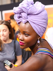 Lupita Nyong'o matched her lavender head wrap with a pair of gemstone drop earrings by Graziela Gems for the premiere of 'Queen of Katwe.'