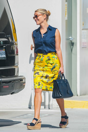 Reese Witherspoon was cool and stylish in a sleeveless navy button-down by Draper James while out and about.