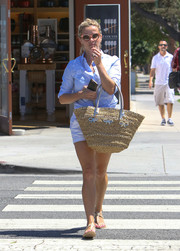 Reese Witherspoon looked very summery sporting this pastel-blue button-down, shorts, and straw tote combo.