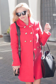 Reese Witherspoon donned a bright red coat with gold button details for a chic outfit while out and about.