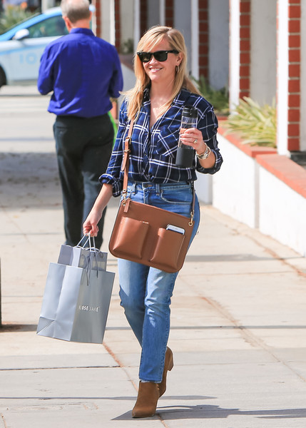 Reese Witherspoon accessorized with a camel-colored leather messenger bag.