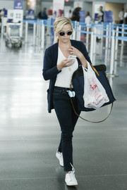 Reese Witherspoon was spotted at JFK wearing a dark blue cardigan over a white shirt.