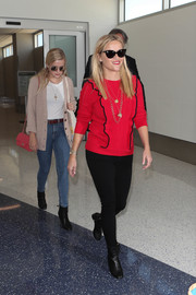 Reese Witherspoon kept it chic in a red ruffle sweater by Draper James during a flight out of LAX.