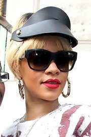 Rihanna paired a kooky visor and oversize gold hoops with modified cateyes.