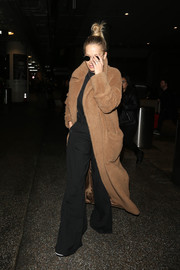 Rita Ora looked super cozy in a brown teddy bear coat while catching a flight at LAX.