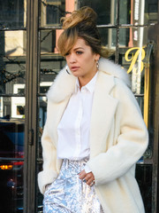 Rita Ora headed out in New York City wearing a white button-down shirt under a fur-collar coat.