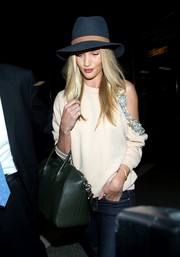 Rosie Huntington-Whiteley styled her travel outfit with a blue and brown walker hat by Janessa Leone.