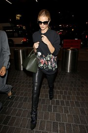 Rosie Huntington-Whiteley teamed a floral sweater with leather pants for her airport look.