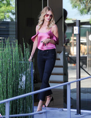 Rosie Huntington-Whiteley was a vision in her rose-colored satin top by The Reformation that featured cut-out draped sleeves.  The model styled her look with black jeans and strappy sandals.