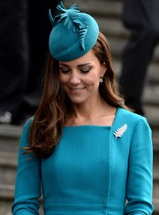 Kate Middleton teamed a fern-embellished teal hat with a long-sleeve dress for church service in New Zealand.