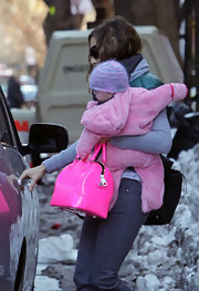 "SJP leaves her NYC home with one of her twin daughters in her arms while fighting the snowy weather. She also managed to carry a cute hot pink ""Bonnie"" bag all in the same hand - what a multi-tasker."