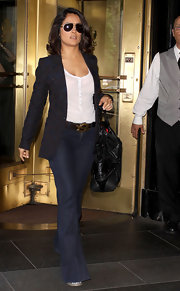 Salma wore flared jeans with a leather YSL logo belt and an embroidered blazer.