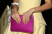 Samantha Barks added a spice of color to her pastel yellow cocktail dress by pairing it with this fuchsia clutch.
