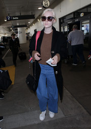 Saoirse Ronan kept her traveling feet comfy in white leather sneakers by Gucci.