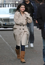 Selena stays warm with this classic khaki trench coat.