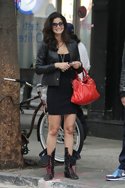 Shermine punches up her all-black outfit with a red studded City bag.