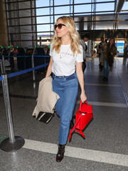 Sienna Miller sported a La Ligne T-shirt printed with the words 'I will tell on you' while catching a flight out of LAX.