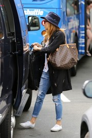 Sienna Miller prepared to catch a flight carrying a Louis Vuitton monogram bag.