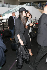 Sofia Carson accessorized with a chic black python bag during a flight out of LAX.