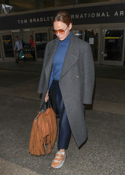 Stella McCartney layered a gray wool coat over a blue turtleneck and trousers for a flight to LAX.