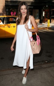 Miranda Kerr styled her simple outfit with a beige cross-body tote. The neon-pink handles added a fun touch.