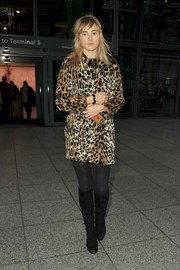 Suki Waterhouse rocked knee-high black suede boots with her stylish coat.