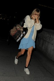 Suki Waterhouse stepped out wearing a fluffy cream cardigan over a turquoise dress.