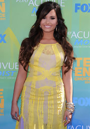 Demi Lovato wore a lacy yellow frock with an asymmetrical hem to the Teen Choice Awards. She finished off the look with layered bangles and a half up-half down 'do.