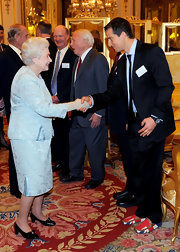 Formal shoes would have been more apt for a Buckingham Palace event than the casual Union Jack loafers Bear Grylls wore, but at least his patriotic ardor was admirable (and the loafers were cute, too).