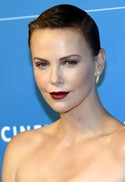 Charlize Theron's lips simple popped in a red hue, with minimal makeup and slicked back hair.
