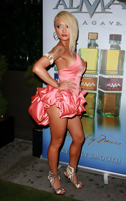 Tila made a statement in a coral pink ensemble and a bold pair of futuristic, strappy metallic heels.
