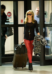 Ashley Tisdale added a burst of red to her travel attire with a pair of sleek leather pants.