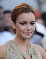 Lily Collins showed off her darling earrings, which she paired with a classic bun.