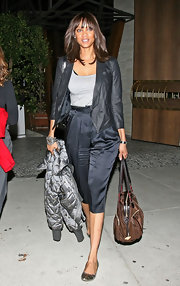 Tyra Banks donned gold metallic ballet flats with her high waist cropped satin trousers.