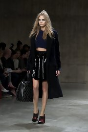 Cara Delevingne walked the runway carrying a stylish weekender tote at the Unique show at LFW.