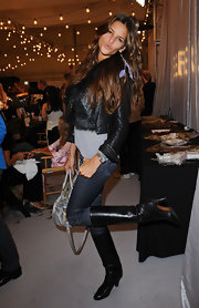 Izabel poses for the camera in her stylish cropped long sleeve leather jacket layered over fur and a gray tee.